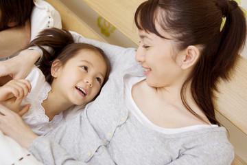 ベッドで会話する母と娘