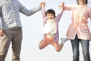 両親に手を引かれてジャンプする女の子