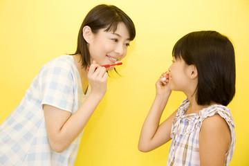 歯磨きをする女の子と母親
