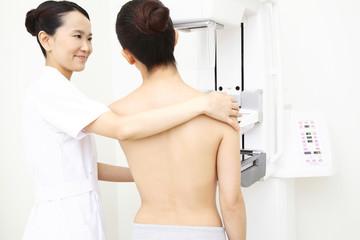 乳がんの検査を受ける患者とサポートする技師
