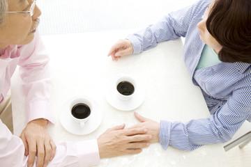 手を重ねている夫婦とコーヒーカップ