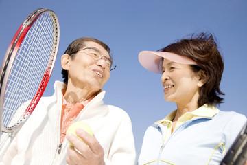 テニスラケットを持っている夫婦