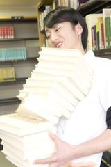 山済みの本を抱える学生