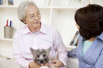 居間で話をしている夫婦と犬
