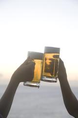 ビールで乾杯をする2人の女性の手元