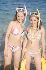 シュノーケリングをしようと海へ入る水着姿の女性2人
