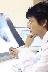 レントゲン写真を見つめる男性医師