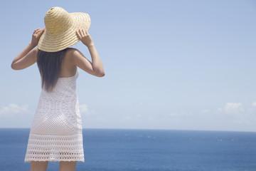 麦わら帽子被って海を眺める女性の後ろ姿