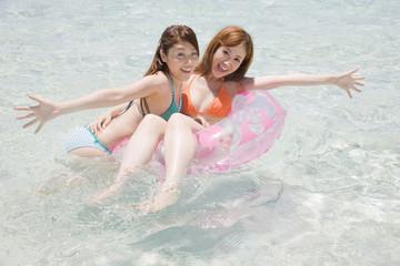 浮き輪に乗る水着女性と浮き輪につかまる水着女性
