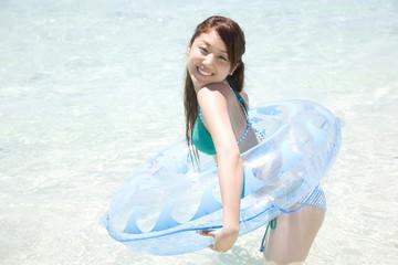 海に入り浮き輪を持つ水着女性