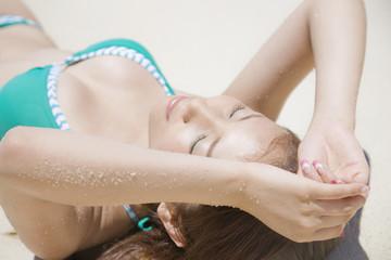 砂浜で寝転がる水着女性
