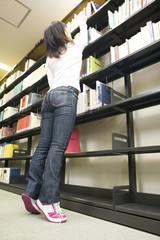 背伸びして本をとる学生