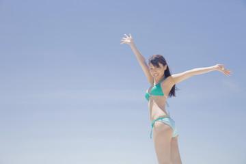 青空に両手を挙げる水着女性