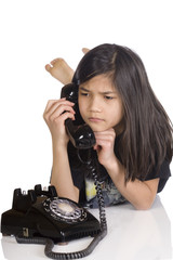 Girl talking on rotary phone, worried expression