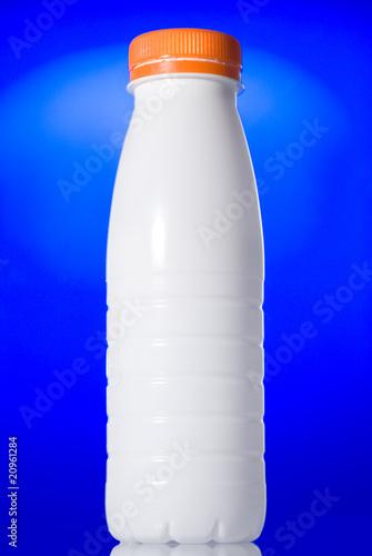 Leinwandbild Motiv White milk bottle isolated on blue
