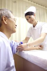 患者の腕をまくる看護師