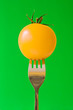 fork with yellow tomato, isolated on green background