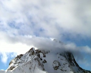Clouds moving over snow capped mountain, Les Deux, France