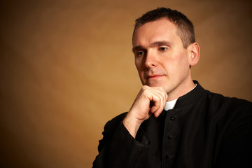 Priest with hand under chin