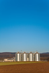 beautiful landscape with silo and snow white acre with blue sky