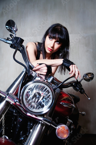 A sexy brunette woman sitting on a  motorbike