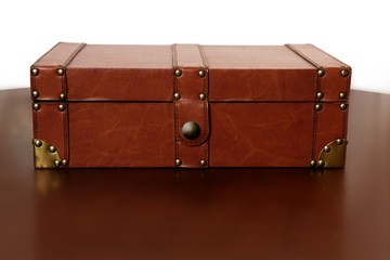 Brown leather suitcase over warm wood