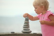 little girl building construction from pebble stones.