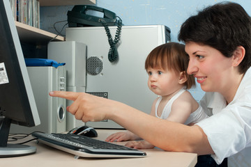mother with little daughter working on computer