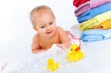 little boy playing with ducks and bubbles next to the towels