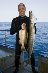 fisherman holds two big fish up