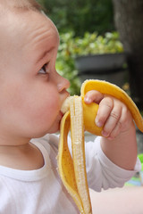 child eat yellow banana in outdoors