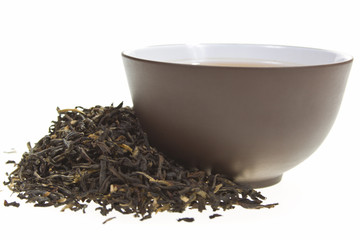 clay cup in dried tea leaves on a white background