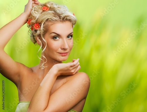 Beautiful young woman with fresh flowers in her hair.