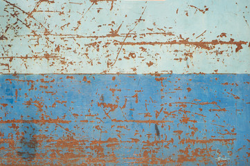 Striped two-tone painted blue metal surface with rust scrapes