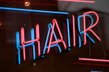 A neon sign in the window or a hair salon