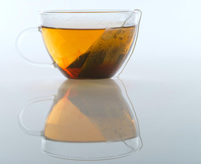 Glass cup of tea on a white background
