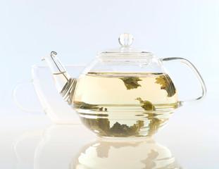Glass tea pot with tea and cup