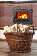 birch firewood in a wicker basket, fire in a stone stove