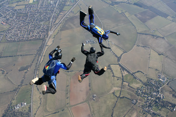 Camera man filming two skydivers