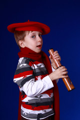 Little boy in red scarf and beret with a spyglass
