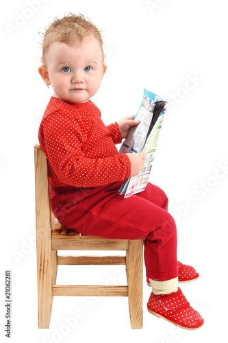 Baby sitting on chair reading a magazine isolated on white