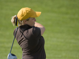 Female College Golfer Swinging Fairway Wood