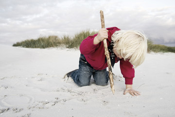 Young blond boy kneels at the beach of Prerow