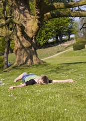 Girl lying in the grass in the park of egeskov castle, Denmark