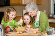 Grandmother teaching kids to bake