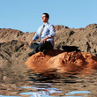 Successful businessman relaxing on the rocks