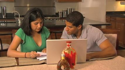 Latino couple doing bills at laptop - 112