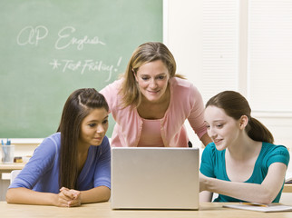 Teacher helping students on laptop