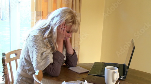 Frustrated woman working at a laptop at home