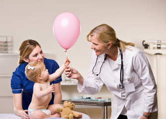 Doctor handing baby girl balloon